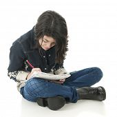 A attractive young teen sitting on the floor, intently writing on a note pad on her lap.  On a white background.