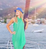 Beautiful blond girl standing on the deck of luxury sailboat in bright sun light, spending leisure time on the sea, enjoying summer vacation concept