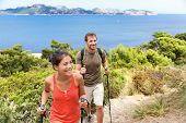 Hikers hiking in Mallorca, mediterranean Europe. Young adults couple walking in beautiful nature landscape on the coast of Mallorca, Balearic Islands, Spain. Famous European summer destination.