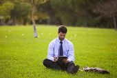 Businessman using a digital tablet at the city park