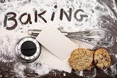 Word baking written in white flour and cooking utensils on a wooden table