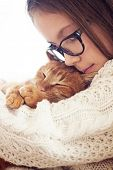 foto of ginger  - Cute ginger cat sleeps warming in knit sweater on his owner - JPG