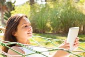 Woman Using Digital Tablet In Hammock At Park