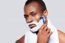 stock photo of shoulder-blade  - Handsome shirtless African man shaving his face and looking at camera while standing against grey background - JPG