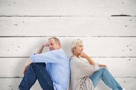 picture of not talking  - Upset mature couple not talking against white wood - JPG
