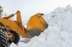 stock photo of bulldozers  - A bulldozer clears snow drifts after the storm - JPG