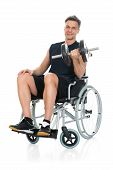stock photo of disability  - Smiling Disabled Man On Wheelchair Working Out With Dumbbell Over White Background - JPG