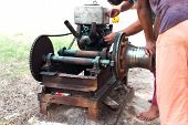 picture of carburetor  - Man working on repairing an old engine in blur background - JPG