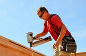 picture of top-gun  - Building contractor worker with a air nail gun nailer working on the corner of the top plate of the first floor walls on a new home construciton project - JPG