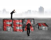 foto of yell  - Boss using speaker yelling at employee pushing big jigsaw puzzle concrete blocks with red FEAR word on concrete floor cityscape skyline background - JPG
