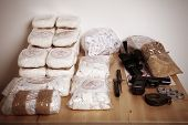 stock photo of smuggling  - Drug packages raw opium drug dozens and weapons seized by police - JPG