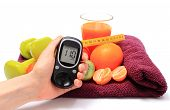 foto of immune  - Hand with glucose meter fresh fruits with tape measure glass of juice and green dumbbells for fitness concept for diabetes slimming healthy nutrition and strengthening immunity - JPG