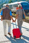 Mature Aged Couple At The Station. Traveling On Vacation