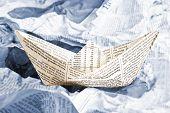 image of newspaper  - An origami newspaper boat over newspapers waves - JPG
