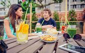 picture of infusion  - Infused fruit water cocktails and green vegetable smoothies over a table with group of young people talking in the background - JPG