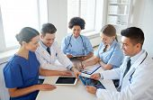 hospital, medical education, health care, people and medicine concept - group of happy doctors with  poster