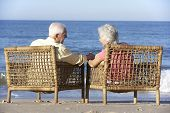 foto of couple sitting beach  - Senior Couple Sitting In Chairs Relaxing On Beach - JPG