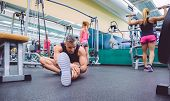 foto of stretch  - Handsome man stretching in a fitness center and two beautiful women doing exercises with dumbbells in the background - JPG