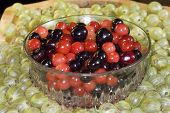 picture of black-cherry  - A bowl of red and black cherries surrounded by green gooseberries - JPG