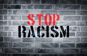 image of racial discrimination  - Stop racism stencil print on white wall background - JPG