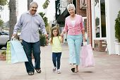 stock photo of granddaughter  - Senior Couple With Granddaughter Carrying Shopping Bags - JPG