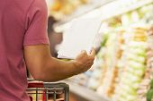 picture of supermarket  - Close Up Of Man Reading Shopping List In Supermarket - JPG