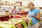 stock photo of supermarket  - Woman At Fruit Counter In Supermarket - JPG