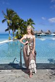 stock photo of infinity pool  - The woman in a long sundress before infiniti pool overlooking the sea - JPG