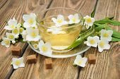 stock photo of jasmine  - A cup of jasmine tea with jasmine flowers on a wooden background - JPG