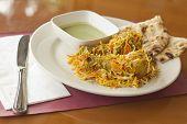 stock photo of biryani  - Indian biryani chicken with naan and mint coriander chutney sauce - JPG