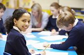 stock photo of 11 year old  - Portrait Of Pupil In Classroom With Teacher - JPG