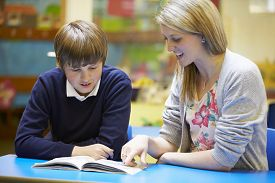stock photo of classroom  - Teacher With Male Pupil Reading At Desk In Classroom - JPG