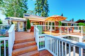 Cozy Screened Walkout Deck With Patio Area And White Railings Staircase. poster