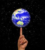 A photo of a woman balancing the globe on her finger