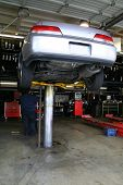 A photo of a car on a lift getting repaired