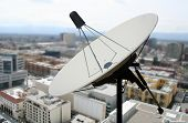 A photo of a satellite dish against a city background