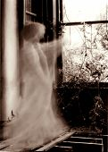 stock photo of derelict  - the ghost of a woman points out of the window of an old derelict house  - JPG