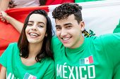 Soccer Fans From Mexico With Mexican Flag Looking At Camera Outdoors At Stadium poster