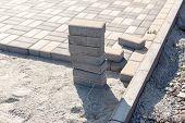 Постер, плакат: Construction of a new pavement of paving slabs closeup detail Pavement cobblestone blocks construct