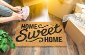 Woman Wearing Sweats and Untying Pink Shoes Near Home Sweet Home Welcome Mat, Moving Boxes and Plant poster