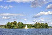 Landscape Of Lake With White Yacht On Bright Sunny Summer Day. Blue Sky With White Clouds Over Big L poster