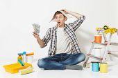 Shocked Man In Newspaper Hat Holds Bundle Of Dollars, Cash Money. Instruments For Renovation Apartme poster