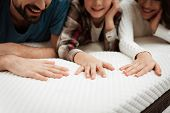Young Couple Together With Their Young Son Test The Material Of The Mattress For A Touch. Family Buy poster