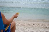 Young Man Guy Sitting On A Deckchair On The Shore Holding A Yellow Starfish In His Hand, Resting Sun poster