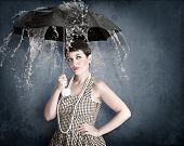 Pin-up girl with umbrella under water splash