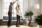 Happy Romantic Couple Having Fun In New Home, Man Holding Womans Hand Up Leading In Dance Enjoying W poster