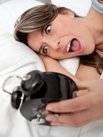 stock photo of running-late  - Woman waking up and running late looking at the alarm clock - JPG