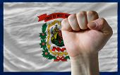 Us State Flag Of West Virginia With Hard Fist In Front Of It Symbolizing Power