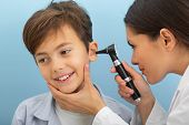 Little Boy While Ear Exam. Ent Doctor Exam Ear With Otoscope On Blue Background poster