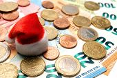 Coins Are On Euro Banknotes. Souvenir Little Red Santa Claus Hat On Money. The Concept Of Christmas  poster